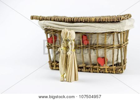 Two Straw Dolls In Front Of An Old Casket