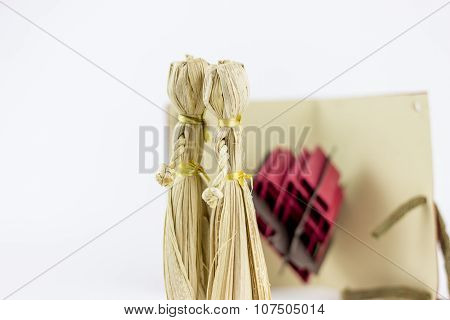 Two Straw Figurines, Kissing On A White Background