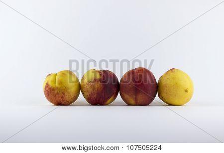 Four Peaches On A White Background