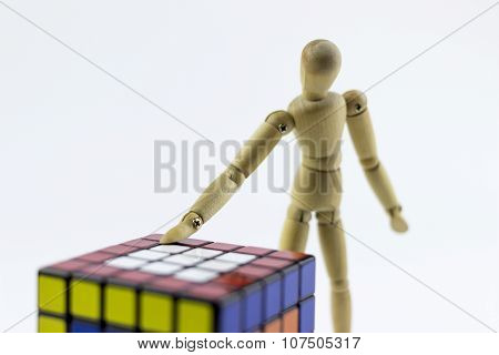 Wooden Puppet Solving A Puzzle Cube