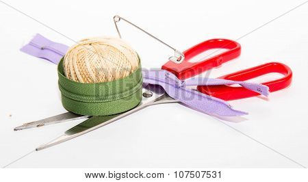 Ball Of Threads With The Thrust Pin, Red Scissors And Two Zippers On A White Background