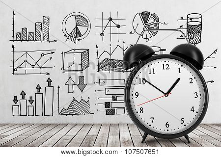 There Are Different Business Charts On The Concrete Wall. An Alarm Clock Is Settled On The Front Vie