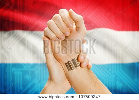 Barcode Id Number On Wrist And National Flag On Background - Luxembourg