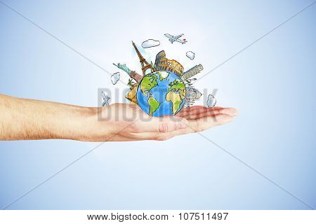 Man's Hand Holding A Globe With Landmarks On A Blue Background