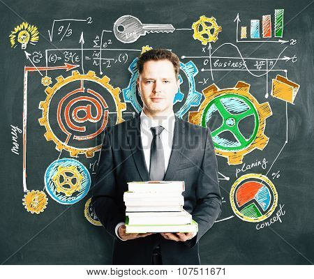 Businessman Holding A Pack Of Books With Blackboard With Business Strategy Concept On The Background