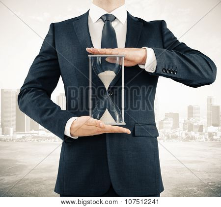 Businessman With Sandglass In The Hands On The City Background, Time Concept