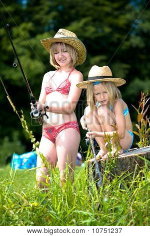 Two Young Girls Fishing At The Lake
