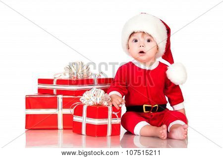 Cute Little Boy Santa  With Gift Boxes On A White Background. Happy  New Year  And Christmas Holiday
