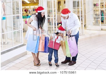 Happy Family Looking At Shopping Bags In The Mall