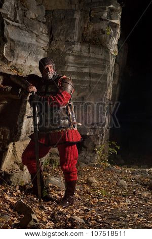 Old Medieval King In Armor With Sword On The Rocks Background.