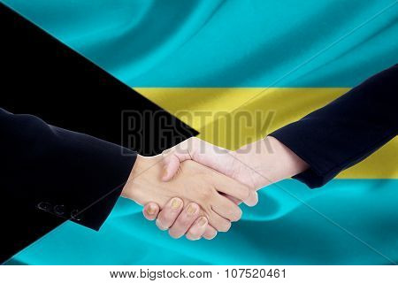 Two People Shaking Hands With Flag Of Bahamas