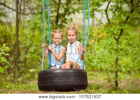 Adorable little girls having fun on a swing outdoors