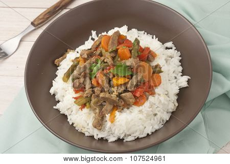a brown bowl of white rice with stir fry beef with bell peppers, asparagus and carrots