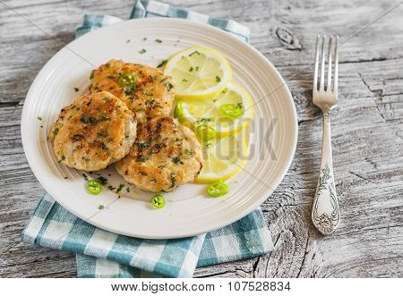 Chicken Cutlets With Lemon And Herbs On A White Plate On A  Wooden Background