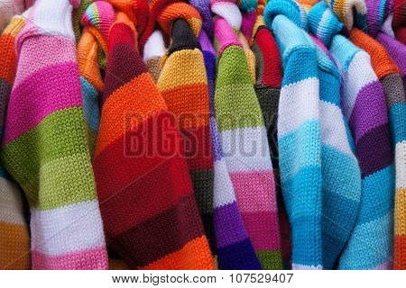 Colorful striped pullovers on hangers.
