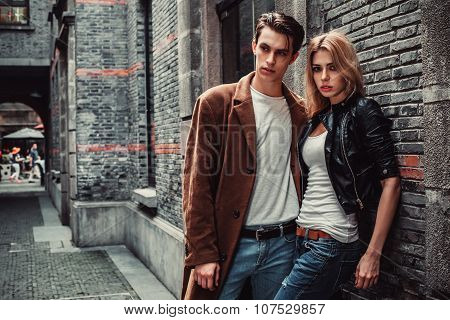 Young trendy man and woman posing in brick walls street