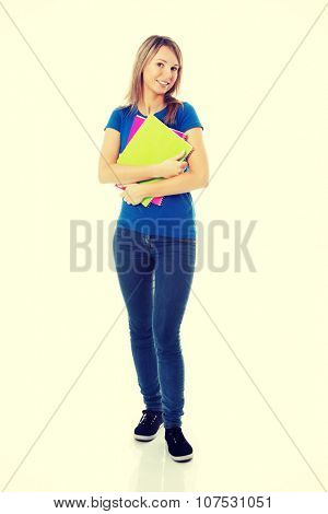 Portrait of a young beautiful female student with workbook.
