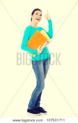 Young beautiful student woman holding workbook and pointing up.