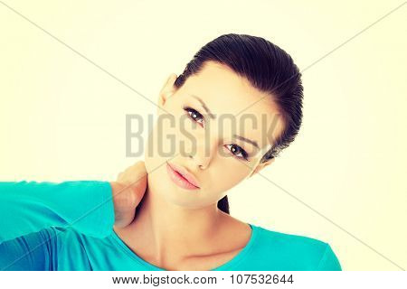 Young woman holding hand on her neck. Neck pain concept