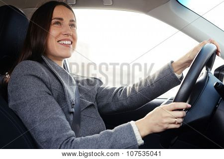 beautiful young woman driving a car and smiling