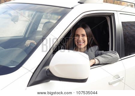 alluring young woman driving a car and looking at camera