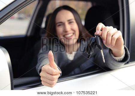 prosperous young woman holding car key and showing thumbs up. focus on the key