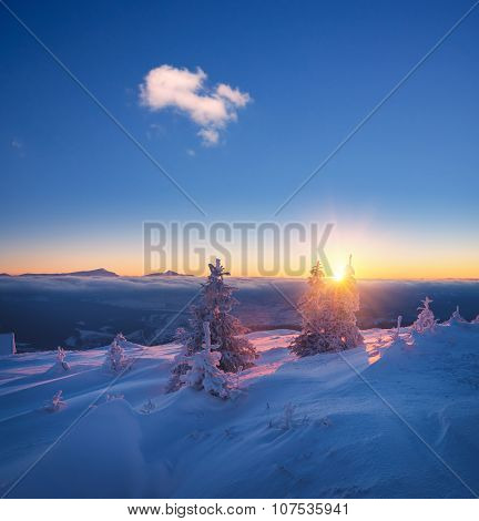 Frosty morning in mountains. Landscape with the rising sun. Snowy winter