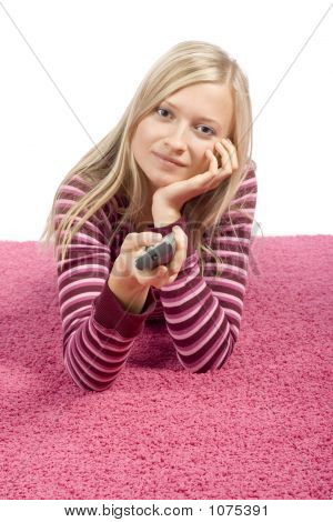 Young Blonde Woman Lying On The Pink Carpet With Remote Control