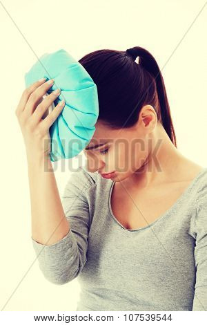 Young beautiful woman is haveng a headache and holding ice bag.