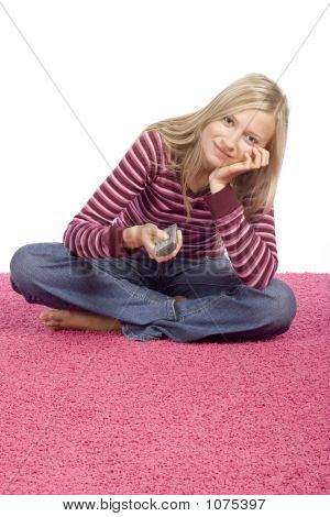 Young Blonde Woman Sitting On The Pink Carpet With Remote Contro