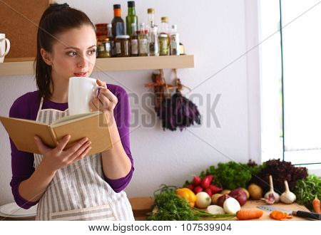 A young woman standing in her kitchen drinking tea and holding a cookbook.