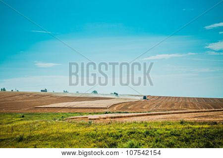 combine harvester on wheat field with  blue sky