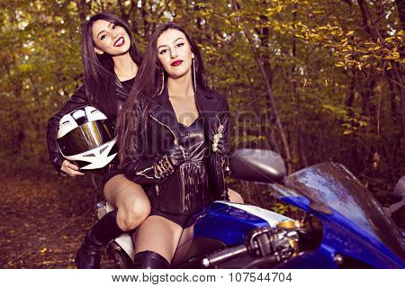 two beautiful women passionate about motorcycles, posing in nature