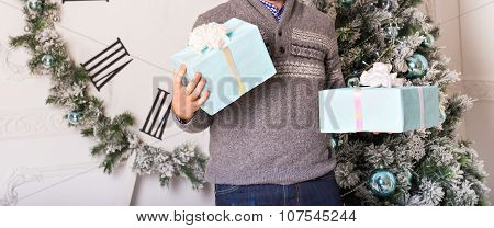 Young man holding gifts in front of Christmas tree
