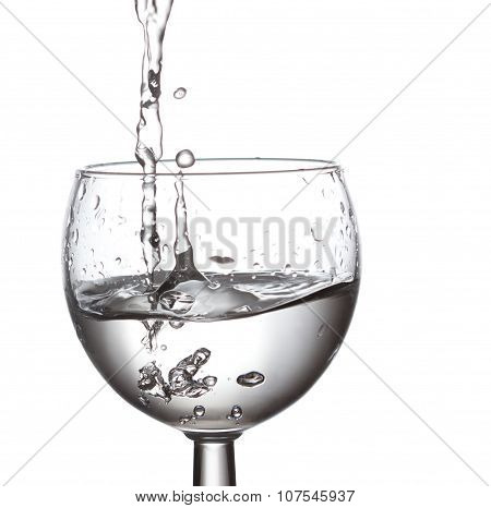 Glass of natural clear drinking water. Splashing liquid, Pouring. white background