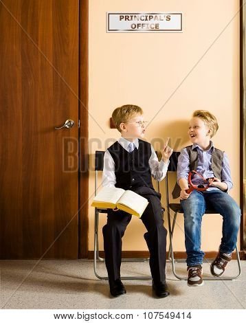 Schoolboys are sitting beside the principal's office
