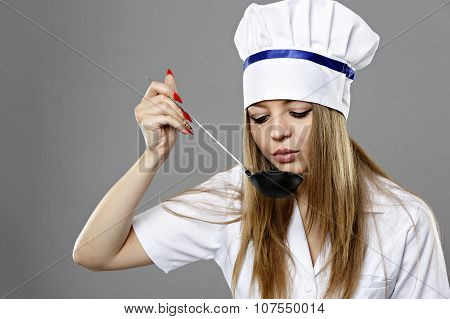 Woman Chef Holding A Spoon And Eating From Spoon. On Gray Background.