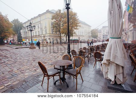 People Walk Under Rain At Market Square With Cobbled Streets And Empty Outdoor Cafe