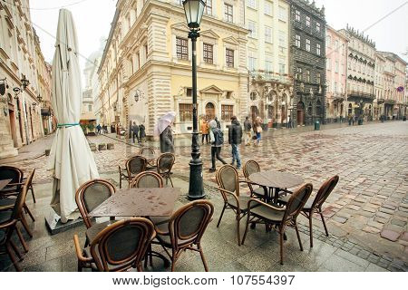 Tourists Walking At Rainy Weather Around Market Square With Empty Outdoor Restaurants