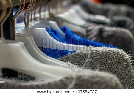 Colored Jackets And Sweaters Hanging On The Hanger