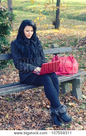 Beautiful Happy Girl Using Notebook While Sitting On Bench In The Park On Sunny Autumn Day
