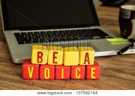 Be a Voice written on a wooden cube in front of a laptop