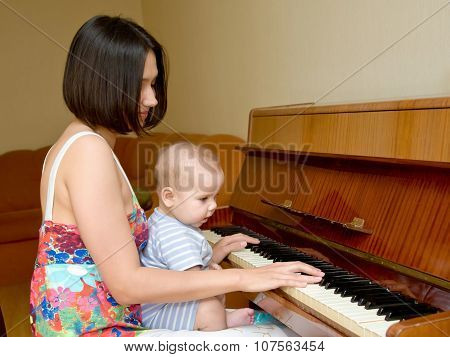 Mother Teaching Baby To Play The Piano.