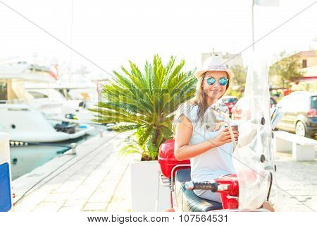 Trendy Woman Drinking Takeaway Coffee Near Her Red Moped On The Waterfront In The Morning