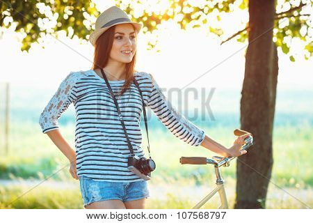 Lovely Young Woman In A Hat Riding A Bicycle In A Park