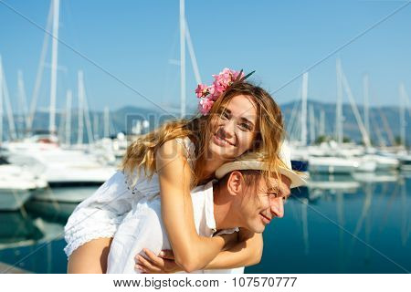 Attractive Young Couple Have Fun In The Marina With Moored Boats On A Luxury Waterfront In Summer Su