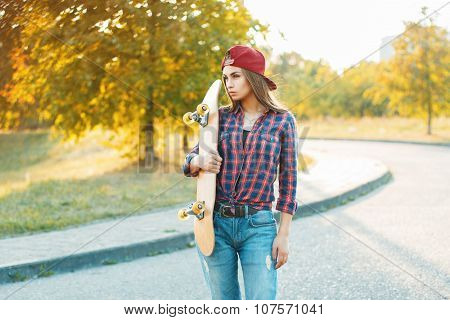 Pretty Woman In Shirt And Jeans Holding A Skateboard. Beautiful Portrait Outdoors Autumn Evening At