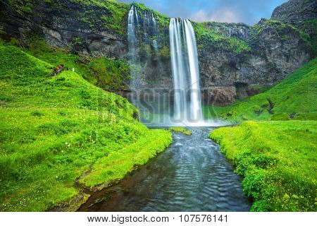 The warm July day in Iceland. Seljalandsfoss waterfall. Rainbow decorates drop of water