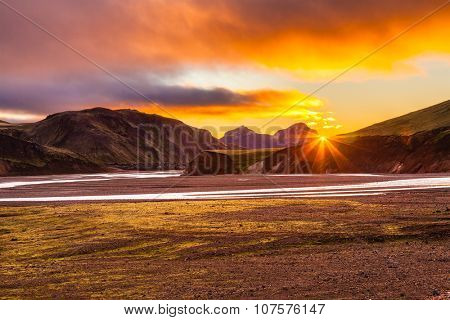 The July morning in the National Park Landmannalaugar, Iceland. Mountains and glaciers covered with warm pink and orange sun