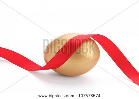 A golden egg with red tape  isolated on white
